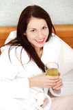 Relaxed woman drinking juice in the bed. Royalty Free Stock Image