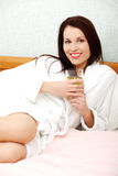 Relaxed woman drinking juice in the bed. Royalty Free Stock Photo