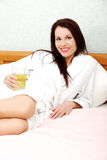 Relaxed woman drinking juice in the bed. Stock Photo