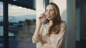 Relaxed woman drinking water near panoramic window. Thirsty lady drinking water stock footage