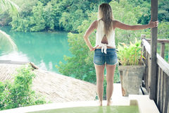 Relaxed Woman at the edge of swimming pool looking at beautiful view Stock Photo