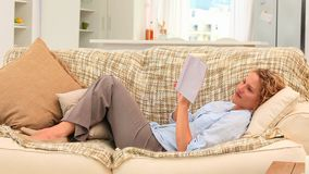 Relaxed woman elongated on her sofa stock footage