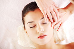 Relaxed woman enjoy receiving face massage. Beautiful young relaxed woman enjoy receiving face massage at spa Royalty Free Stock Photo