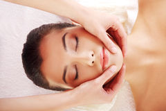 Relaxed woman enjoy receiving face massage. Beautiful young relaxed woman enjoy receiving face massage at spa saloon Royalty Free Stock Photo
