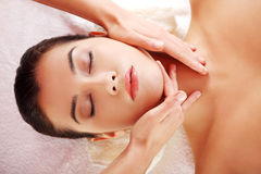 Relaxed woman enjoy receiving face massage. Beautiful young relaxed woman enjoy receiving face massage at spa saloon Stock Photos