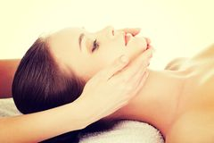 Relaxed woman enjoy receiving face massage. Beautiful young relaxed woman enjoy receiving face massage at spa saloon Stock Image