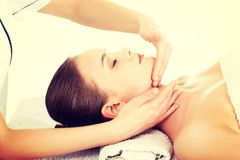 Relaxed woman enjoy receiving face massage. Beautiful young relaxed woman enjoy receiving face massage at spa saloon Royalty Free Stock Photography