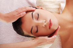 Relaxed woman enjoy receiving face massage at spa. Beautiful young relaxed woman enjoy receiving face massage at spa saloon Royalty Free Stock Images