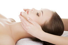 Relaxed woman enjoy receiving face massage at spa saloon. Beautiful young relaxed woman enjoy receiving face massage at spa saloon Royalty Free Stock Image