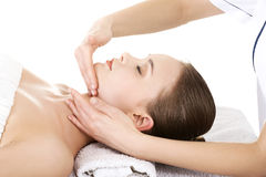Relaxed woman enjoy receiving face massage at spa saloon. Beautiful young relaxed woman enjoy receiving face massage at spa saloon Royalty Free Stock Photo