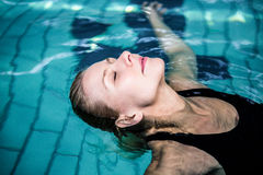 Relaxed woman floating in the swimming pool Royalty Free Stock Images