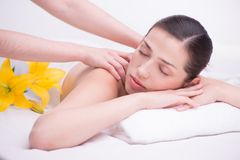 Relaxed woman with flowers in spa center enjoying Royalty Free Stock Image