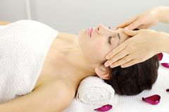 Relaxed woman getting head massage in spa during vacation Stock Photo