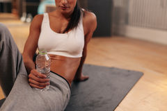 Relaxed woman at gym holding water bottle Stock Photography