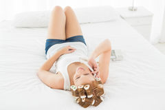 Relaxed woman in hair curlers using phone in bed Royalty Free Stock Photography