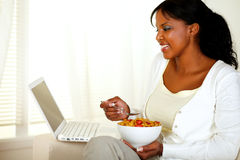 Relaxed woman having breakfast and using laptop Stock Photography