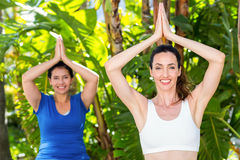Relaxed woman and her trainer doing yoga Stock Images