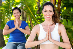 Relaxed woman and her trainer doing yoga Stock Photo