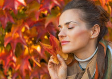 Relaxed woman holding leash in front of foliage Stock Photo