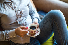 Relaxed woman holding vintage cup of coffee in hands Stock Images