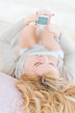 Relaxed woman at home reading a text message in her bright bedro Royalty Free Stock Photography