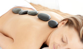 Relaxed woman with hot stones on her back Stock Photography
