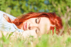 Relaxed woman lays down on grass in nature Royalty Free Stock Images