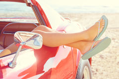 Relaxed woman legs in a car window on the beach Stock Image