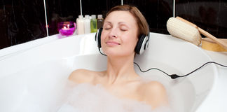 Relaxed woman listening music in a bubble bath Stock Photography