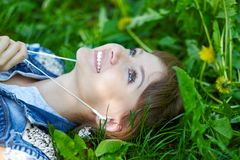 Relaxed woman listening to the music with headphones lying on the grass stock images