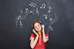 Relaxed woman listening to music in headphones over chalkboard background Royalty Free Stock Photo