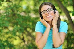 Relaxed woman listening to music in a park with eyes closed Stock Photo