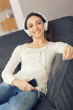 Relaxed woman listening to music on the sofa at home Stock Image