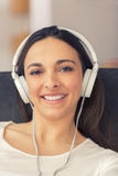 Relaxed woman listening to music on the sofa at home Stock Images