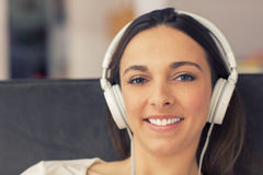 Relaxed woman listening to music on the sofa at home Royalty Free Stock Images