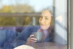Relaxed woman looking outdoors through a window. Portrait of a relaxed woman looking outdoors through a window sitting on a couch in the living room at home Stock Photography