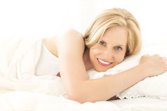 Relaxed Woman Lying On Bed In House Royalty Free Stock Image