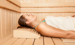 Relaxed woman lying on bench at sauna Royalty Free Stock Photo