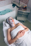 Relaxed woman lying with facial mask in spa Royalty Free Stock Photo