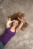 Relaxed woman lying on floor indoors and holding hands up. Stock Photo