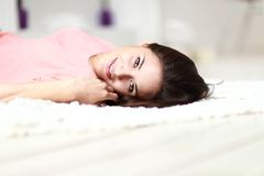 Relaxed woman lying on the floor indoors Royalty Free Stock Photos