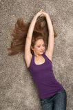 Relaxed woman lying on floor indoors and smiling. Royalty Free Stock Photo