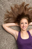 Relaxed woman lying on floor indoors and smiling. Royalty Free Stock Image