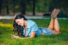 Relaxed woman lying on grass listening to music.  Royalty Free Stock Photos