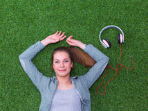 Relaxed woman  lying on the grass near headset Stock Image