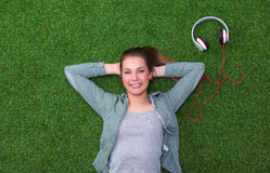Relaxed woman  lying on the grass near headset Stock Photography