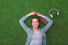 Relaxed woman  lying on the grass near headset Stock Images
