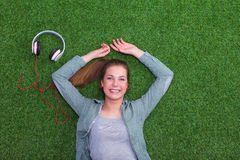 Relaxed woman  lying on the grass near headset Royalty Free Stock Photo