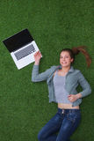 Relaxed woman  lying on the grass near laptop Stock Photos