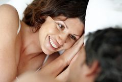 Relaxed woman lying with her husband on bed Stock Photos